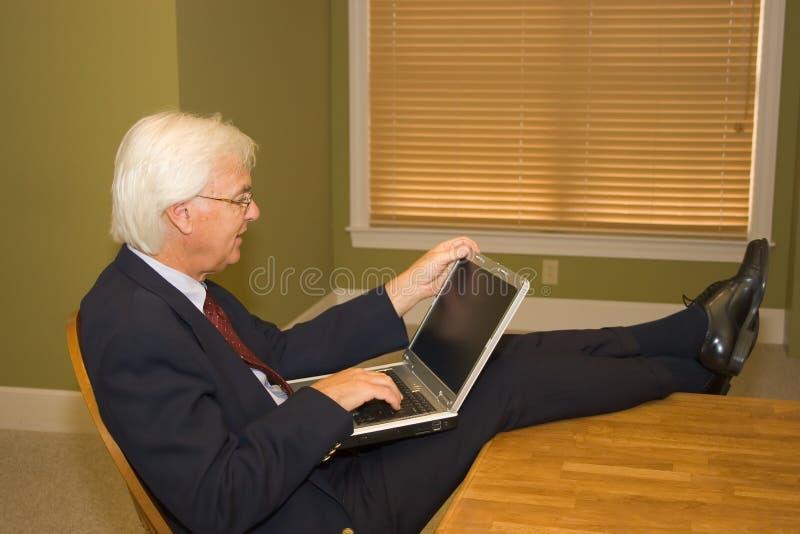 Uomo d'affari maggiore sul computer portatile fotografie stock