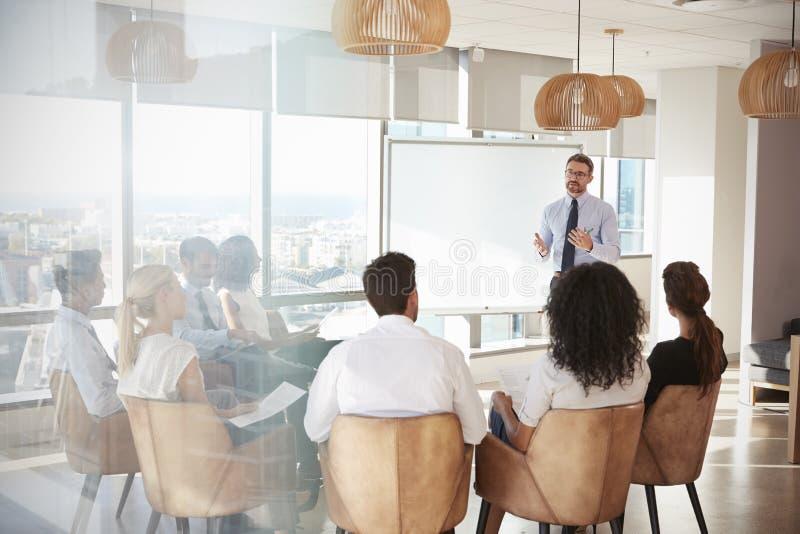 Uomo d'affari Making Presentation Shot attraverso la entrata immagine stock libera da diritti