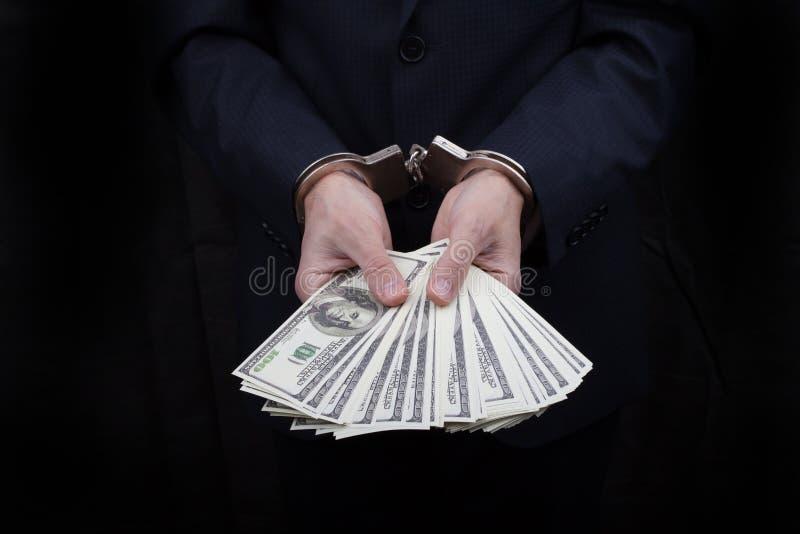Uomo d'affari in manette che tengono dono molti dollari di centinaia fotografia stock