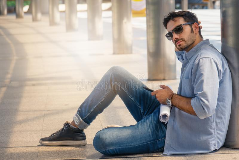 Uomo d'affari maschio che si siede sulla via all'aperto e che per mezzo dello smartphone fotografia stock libera da diritti