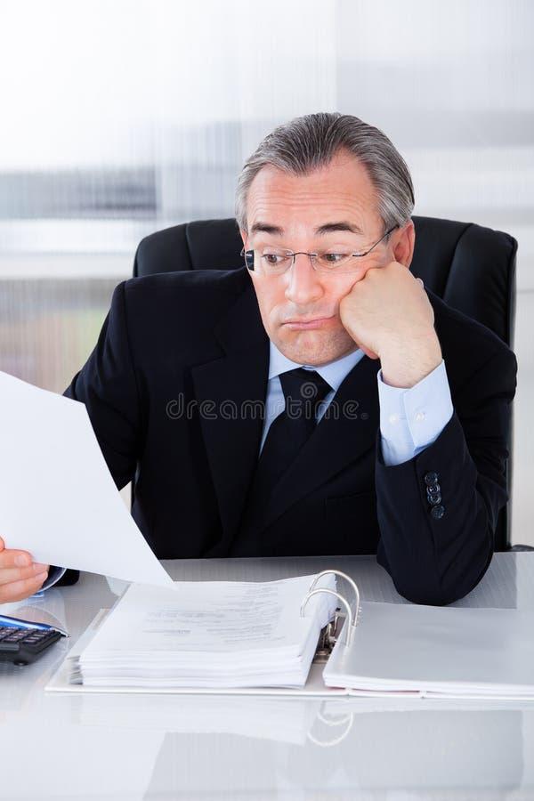 Uomo d'affari maturo annoiato fotografia stock