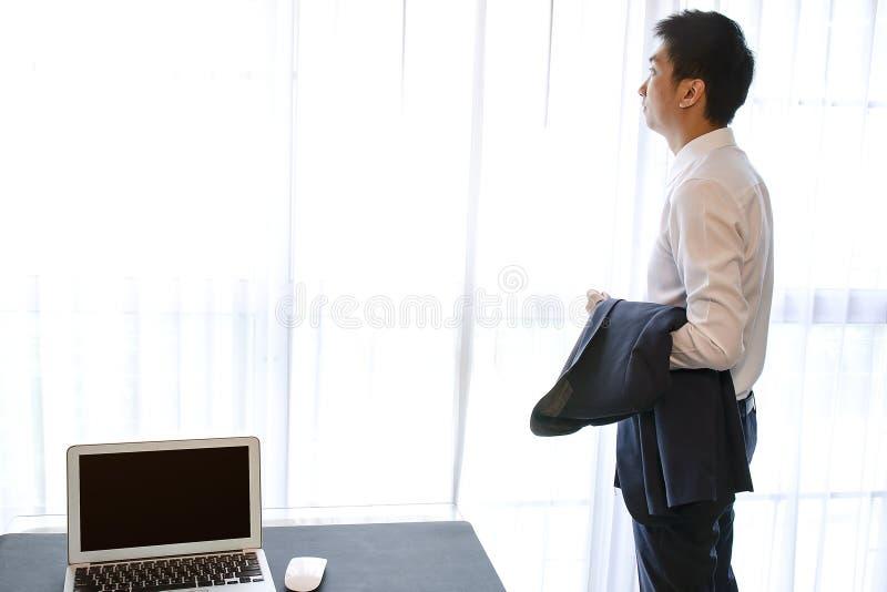 Uomo d'affari maturo che guarda da una finestra da un edificio per uffici immagine stock libera da diritti