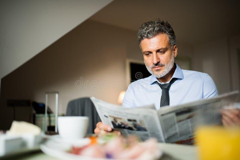 Uomo d'affari maturo che mangia prima colazione in una camera di albergo fotografia stock libera da diritti