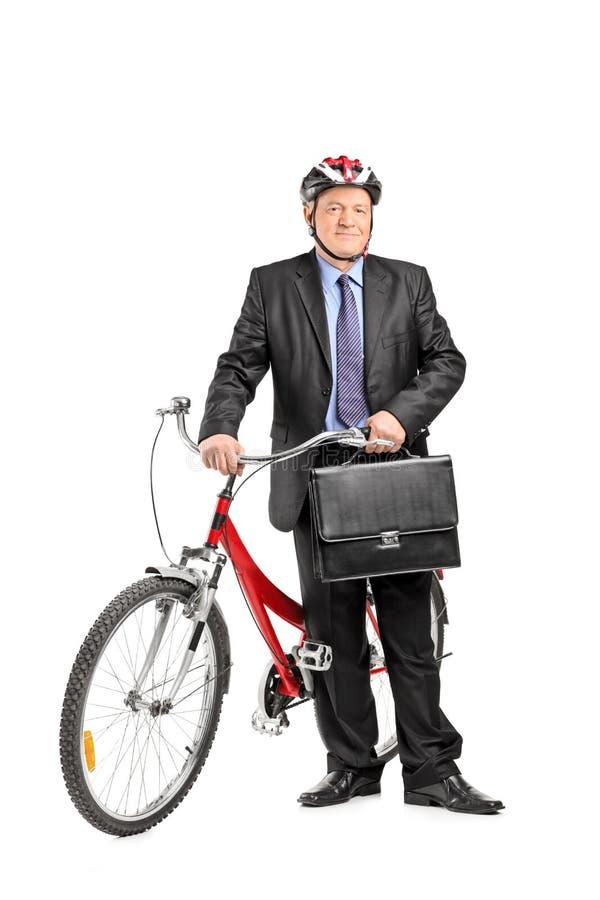 Uomo d'affari maturo che posa davanti ad una bici fotografia stock libera da diritti