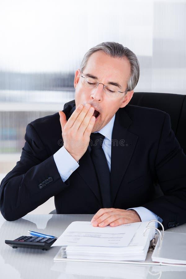 Uomo d'affari maturo che sbadiglia fotografie stock
