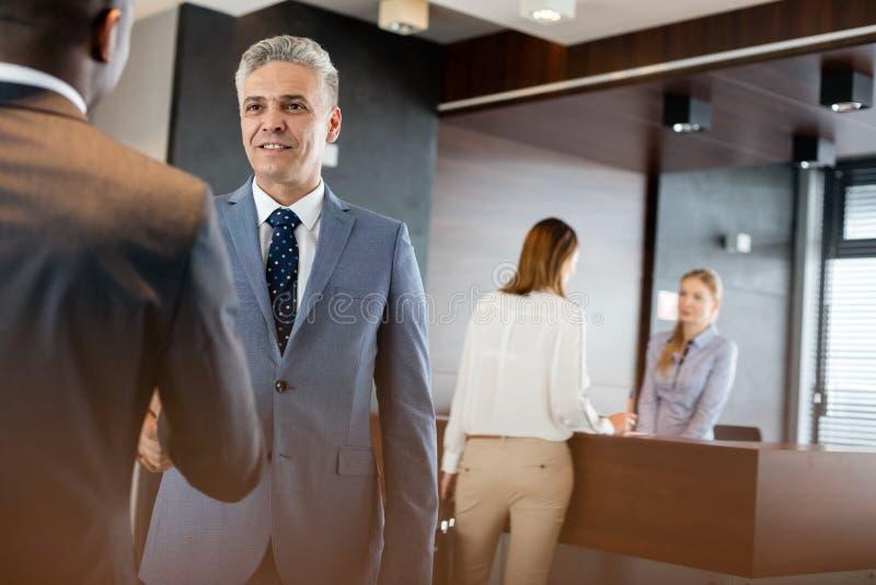 Uomo d'affari maturo che stringe le mani con i colleghi maschii in ufficio fotografie stock