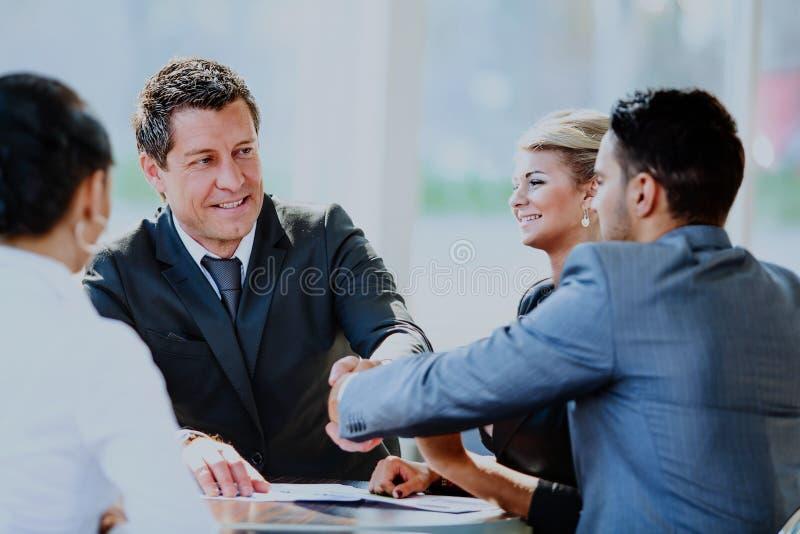 Uomo d'affari maturo che stringe le mani per sigillare un affare con il suoi partner e colleghi in un ufficio moderno fotografia stock libera da diritti