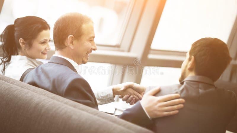 Uomo d'affari maturo che stringe le mani per sigillare un affare con il suoi partner e colleghi in ufficio moderno fotografia stock