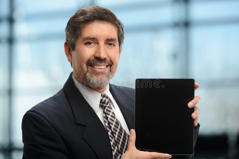 Uomo d'affari maturo che tiene una compressa elettronica fotografia stock