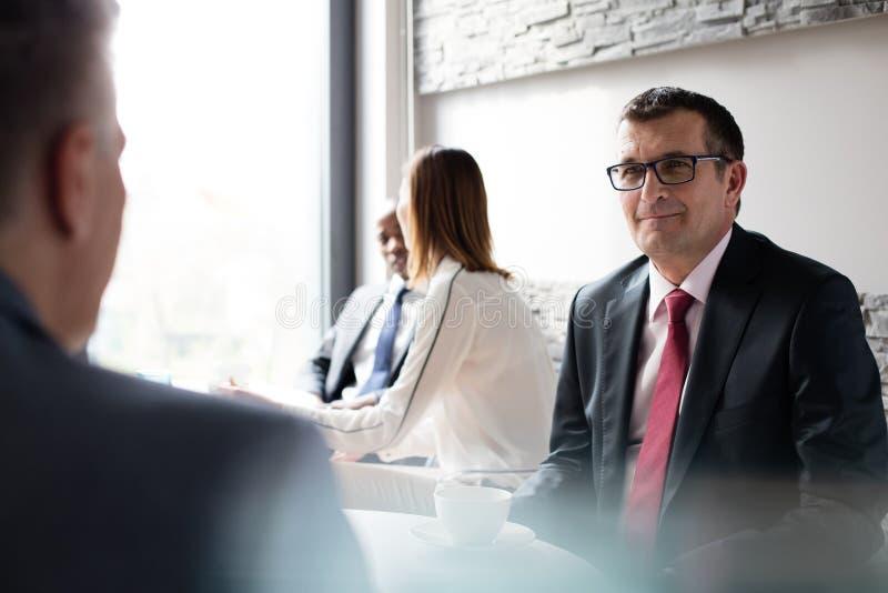 Uomo d'affari maturo con i colleghi nel self-service dell'ufficio fotografia stock