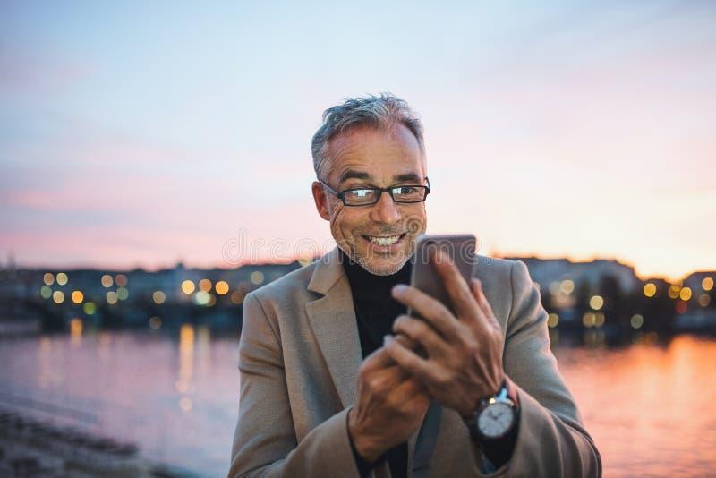 Uomo d'affari maturo con il fiume facente una pausa dello smartphone nella città di Praga, prendente selfie fotografia stock libera da diritti