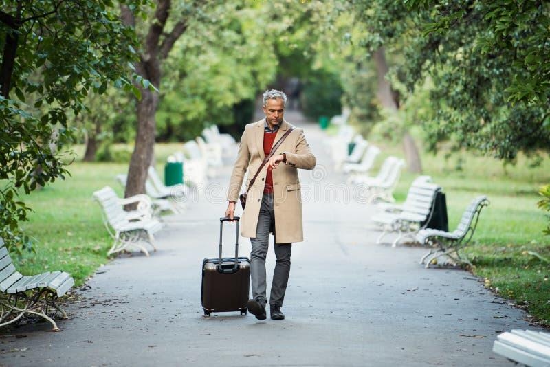 Uomo d'affari maturo con la valigia che cammina in un parco in una città, controllante il tempo fotografia stock libera da diritti