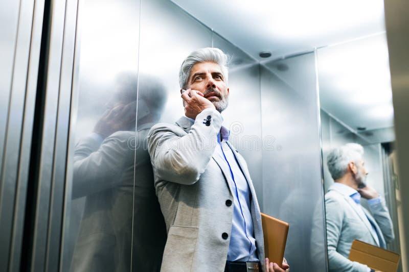 Uomo d'affari maturo con lo smartphone nell'elevatore fotografie stock libere da diritti