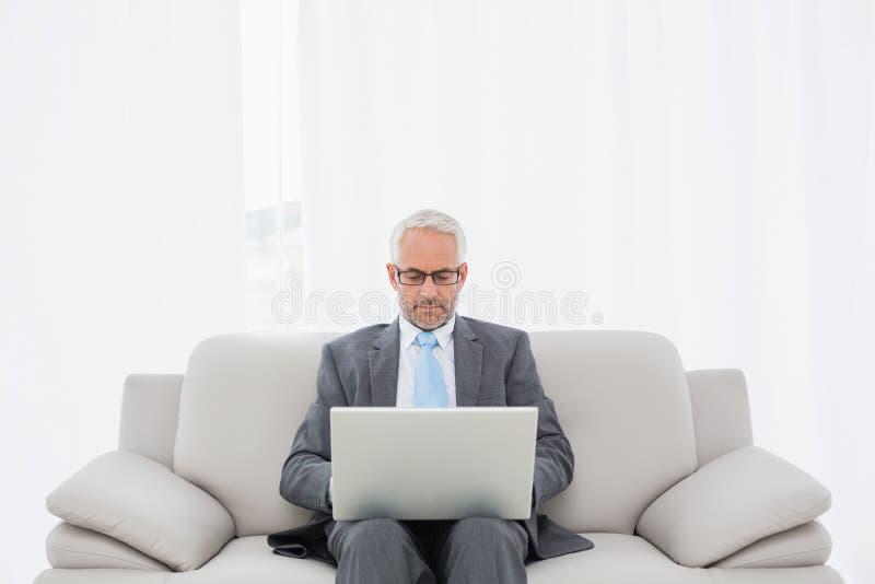 Uomo d'affari maturo concentrato facendo uso del computer portatile a casa immagine stock libera da diritti