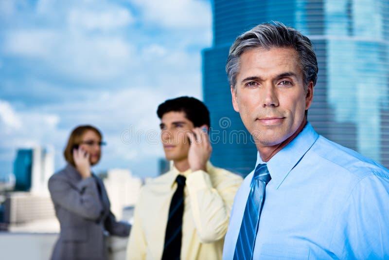 Uomo d'affari maturo e la sua squadra fotografia stock
