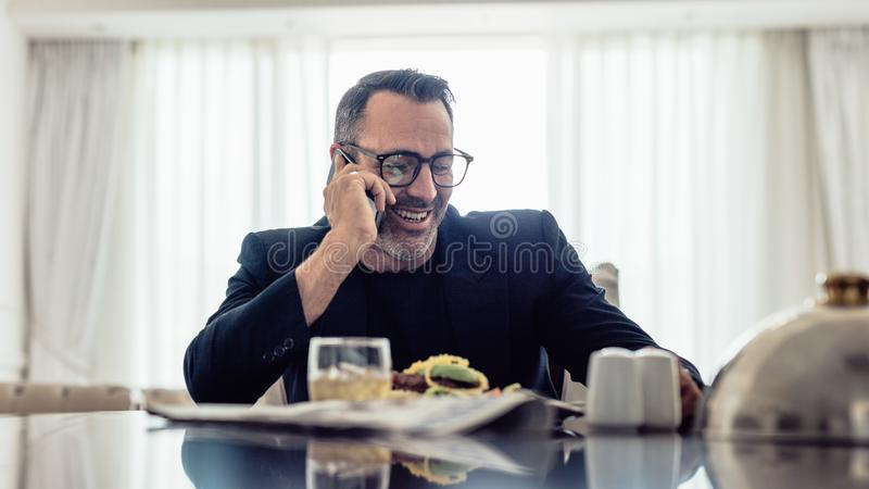 Uomo d'affari maturo felice che parla sul telefono cellulare mentre sedendosi sulla tavola dinning nella camera di albergo Uomo d immagini stock