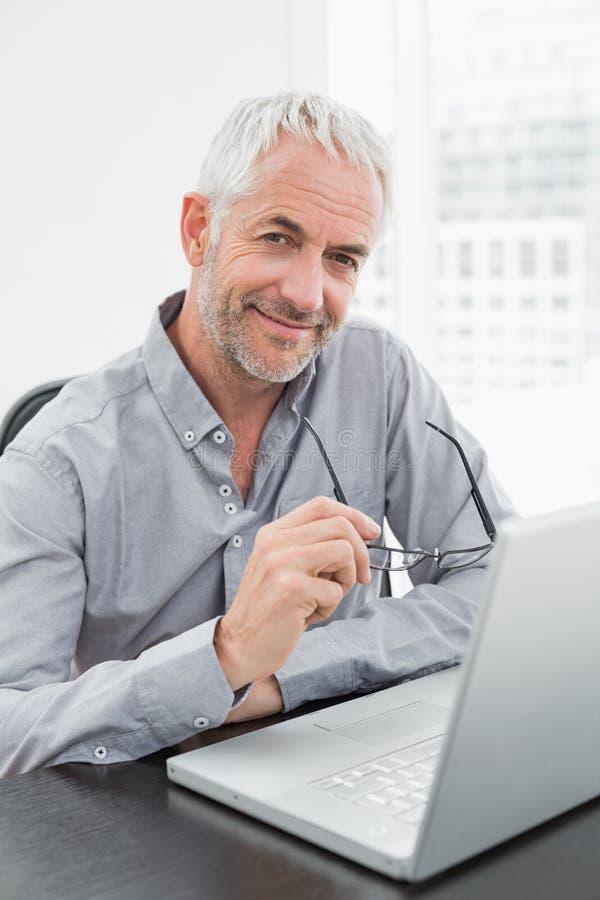 Uomo d'affari maturo sorridente facendo uso del computer portatile in ufficio immagini stock libere da diritti