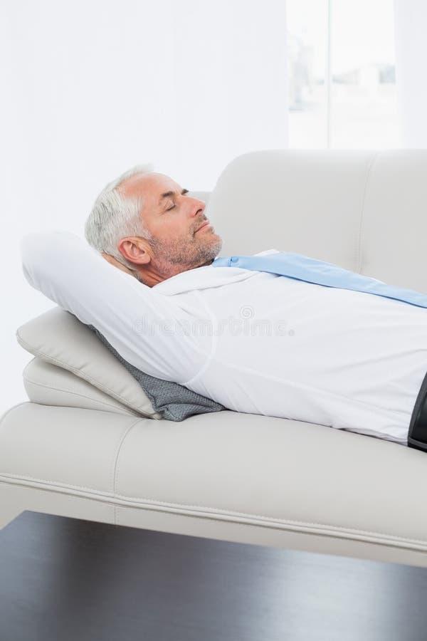 Uomo d'affari maturo stanco che dorme sul sofà in salone fotografia stock libera da diritti