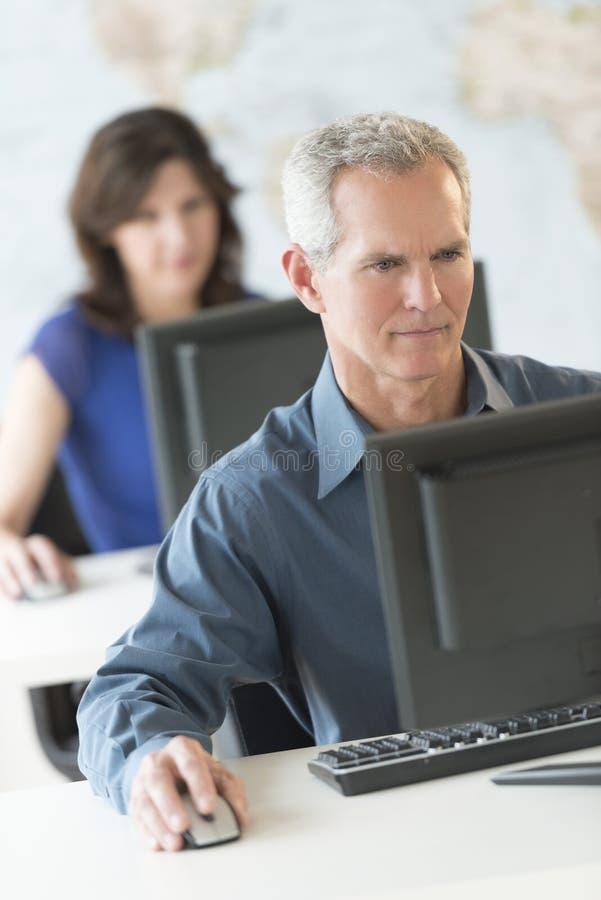 Uomo d'affari maturo Working On Computer in ufficio fotografie stock
