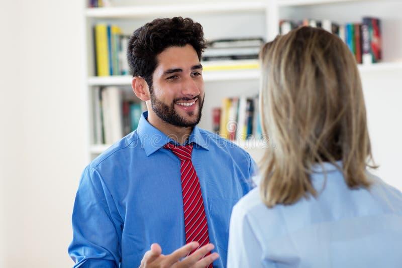 Uomo d'affari messicano che parla con la donna di affari immagine stock