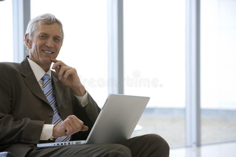 Uomo d'affari messo con il computer portatile fotografie stock libere da diritti