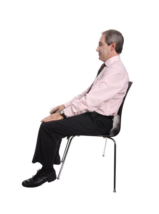 Uomo d'affari messo su una presidenza fotografie stock