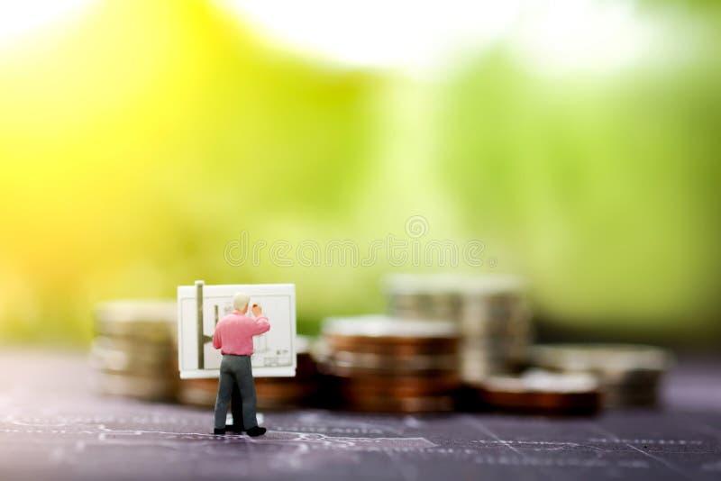 Uomo d'affari miniatura che redige un business plan su un bordo con la pila delle monete immagine stock libera da diritti