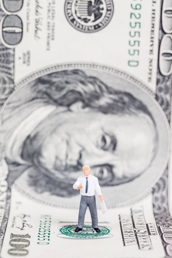 Uomo d'affari miniatura che sta sul dollaro americano fotografie stock libere da diritti