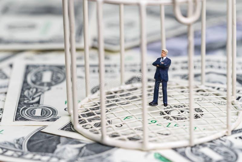Uomo d'affari miniatura dentro il birdcage sul mucchio della banconota del dollaro fotografia stock libera da diritti