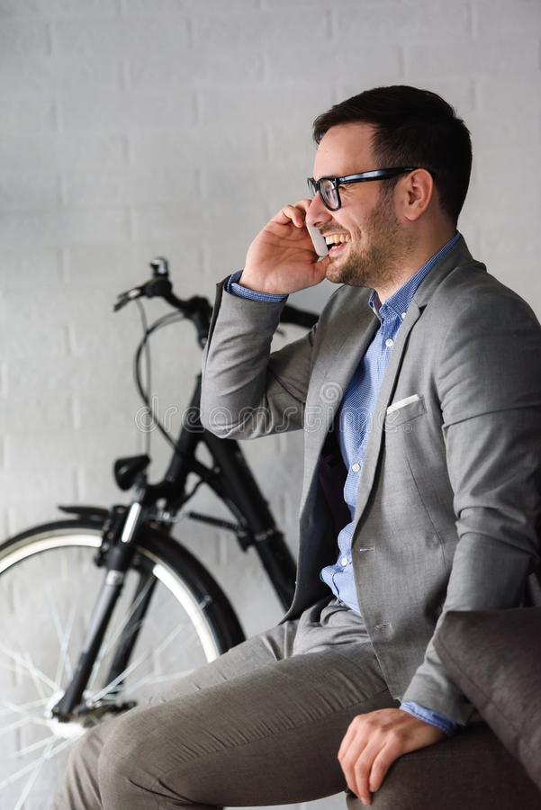 Uomo d'affari moderno bello che per mezzo dello smartphone all'interno immagini stock libere da diritti