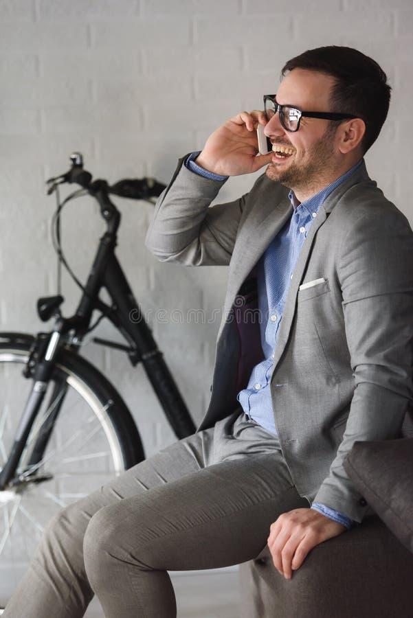 Uomo d'affari moderno bello che per mezzo dello smartphone all'interno immagine stock libera da diritti