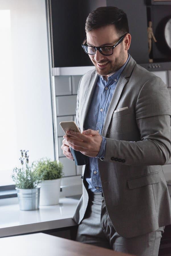 Uomo d'affari moderno bello che per mezzo dello smartphone all'interno fotografia stock libera da diritti