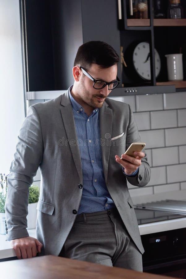 Uomo d'affari moderno bello che per mezzo dello smartphone all'interno fotografia stock