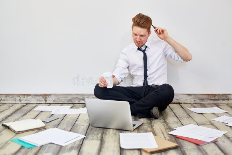 Uomo d'affari moderno Busy Working Sitting sul pavimento immagine stock