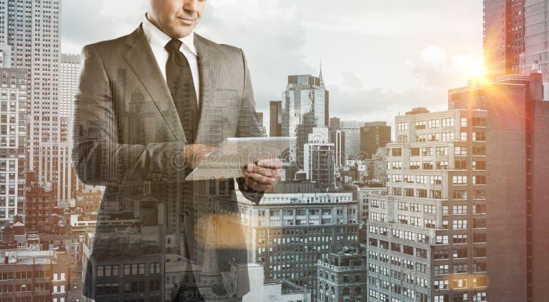 Uomo d'affari moderno con la compressa fotografia stock
