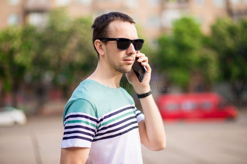 Uomo d'affari moderno dei pantaloni a vita bassa bei con la barba che cammina e che rivolge al telefono cellulare immagine stock libera da diritti
