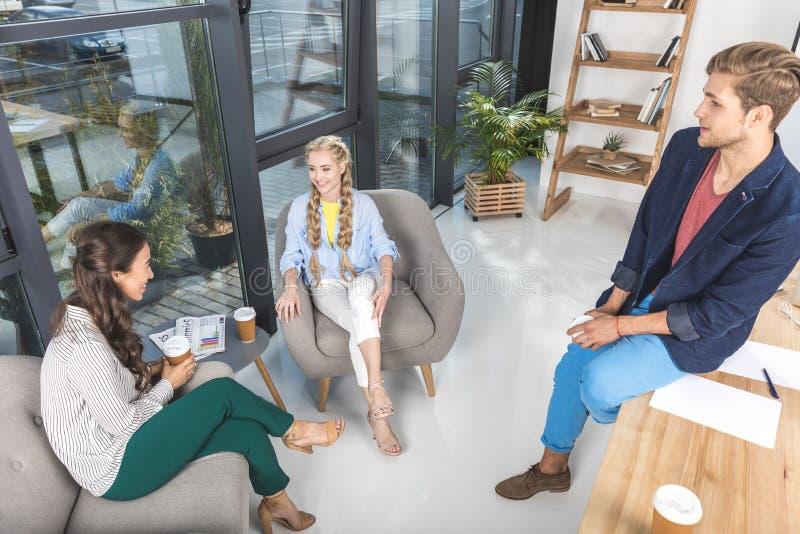uomo d'affari multietnico e donne di affari che riposano mentre avendo pausa caffè fotografia stock