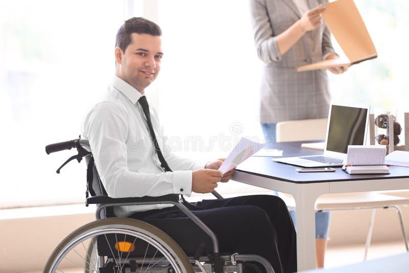 Uomo d'affari nel funzionamento della sedia a rotelle con i documenti in ufficio fotografia stock