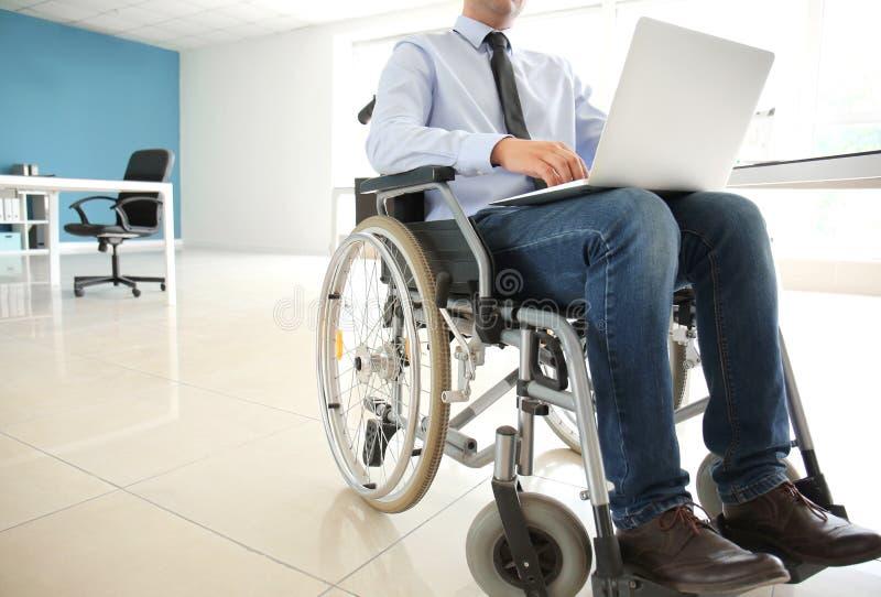 Uomo d'affari nel funzionamento della sedia a rotelle con il computer portatile in ufficio fotografie stock