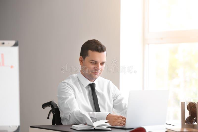 Uomo d'affari nel funzionamento della sedia a rotelle con il computer portatile in ufficio fotografia stock