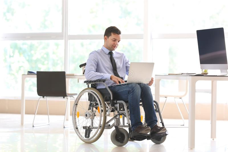 Uomo d'affari nel funzionamento della sedia a rotelle con il computer portatile in ufficio immagini stock libere da diritti