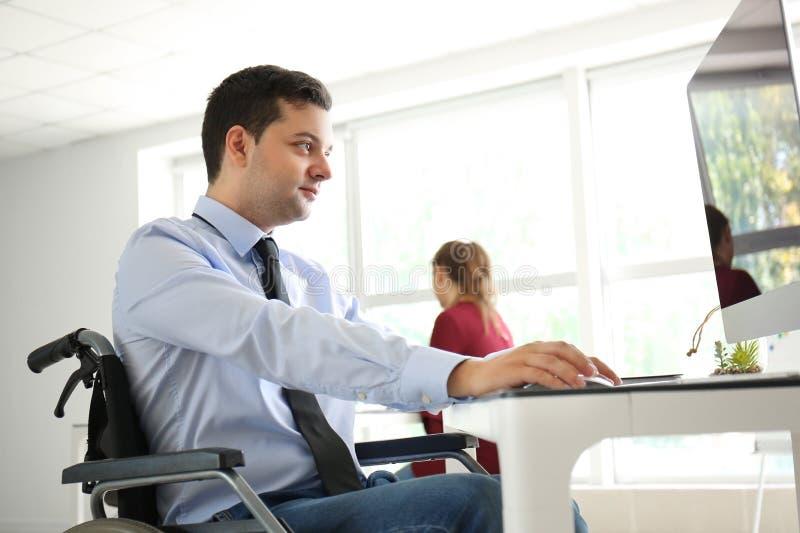 Uomo d'affari nel funzionamento della sedia a rotelle con il computer in ufficio fotografie stock libere da diritti