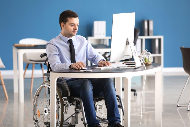Uomo d'affari nel funzionamento della sedia a rotelle con il computer in ufficio fotografia stock