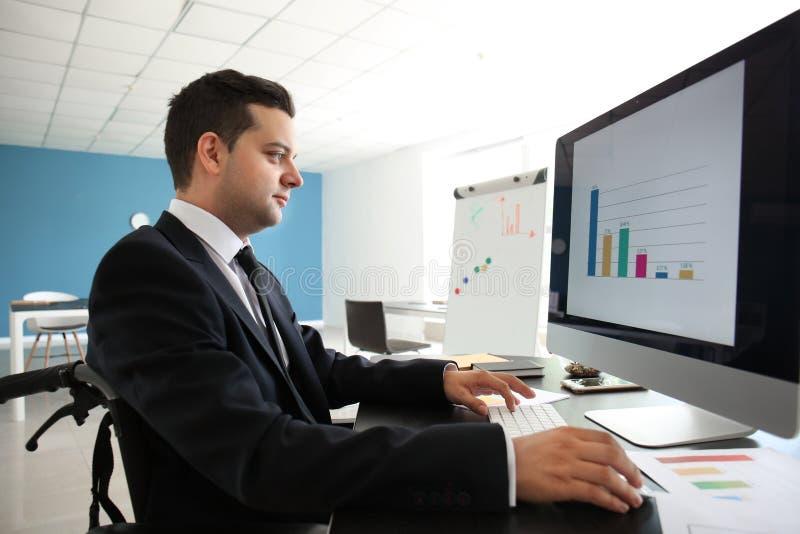 Uomo d'affari nel funzionamento della sedia a rotelle con il computer in ufficio immagini stock libere da diritti