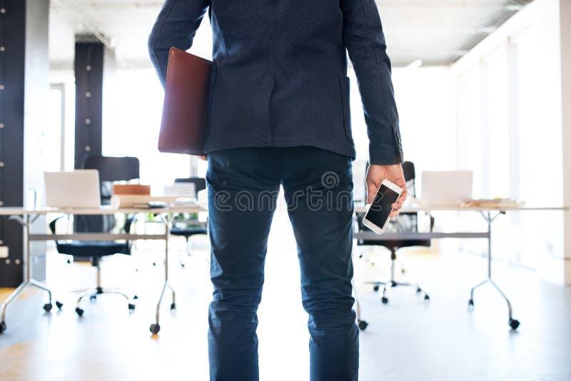 Uomo d'affari nel suo ufficio con lo smartphone e la cartella immagini stock libere da diritti