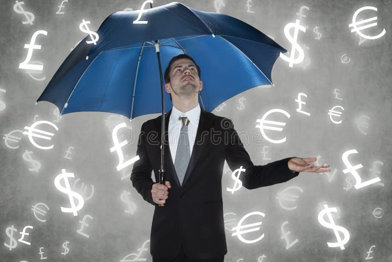 Uomo d'affari nell'ambito delle valute della pioggia fotografia stock