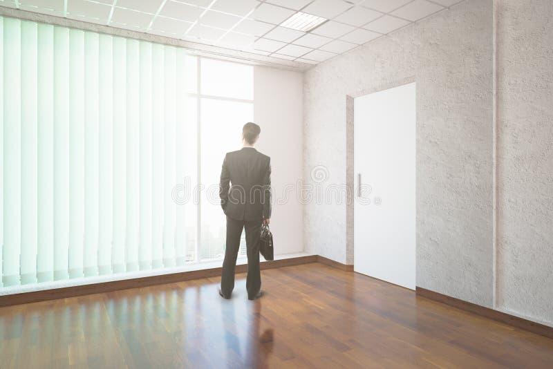Uomo d'affari nell'interno non ammobiliato immagine stock