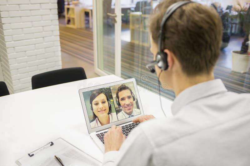Uomo d'affari nell'ufficio sulla videoconferenza con la cuffia avricolare, Skype fotografie stock