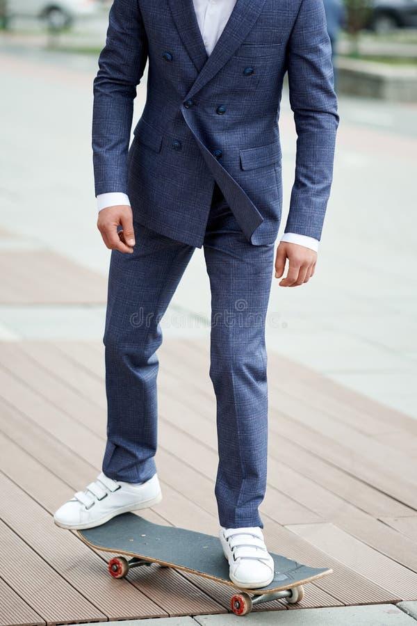 Uomo d'affari nell'usura convenzionale su un pattino Stile dell'uomo d'affari Stile degli uomini immagini stock