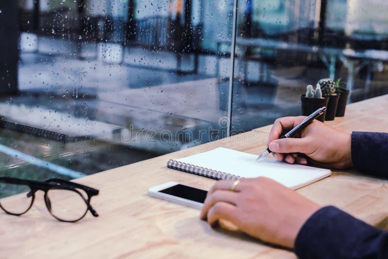 Uomo d'affari nella penna di tenuta nera delle mani della camicia che indica al documento di affari immagine stock libera da diritti